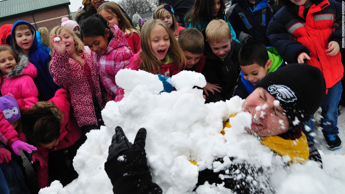 Scotland Elementary School students bury their principal, Tom VanArsdale, in the snow as a reward activity for turning in the most box tops during a school-wide competition in Scotland, Pennsylvania, Friday, January 23.