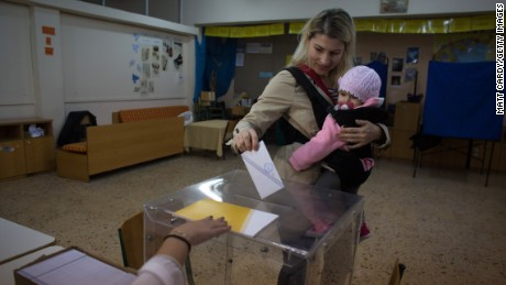 A woman carrying a baby casts her vote in the Greek general election at a polling station in a school in a suburb of Athens on January 25, 2015.