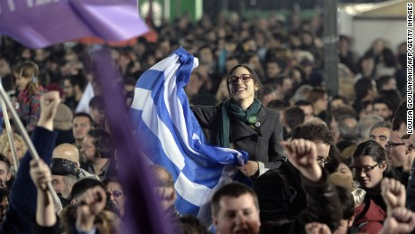 A Syriza supporter celebrates with Greek flag in front of the Athens Academy following victory in the election in Athens on January 25, 2015.