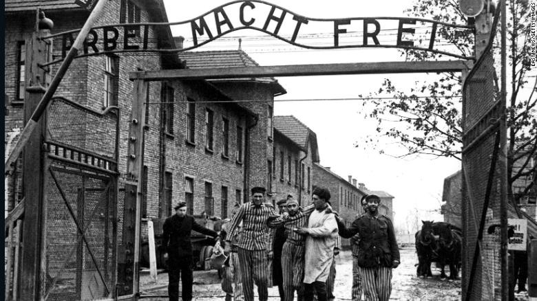"""A doctor, center, with  the 322nd Rifle Division of the Red Army, walks with a group of survivors at the entrance to the newly liberated Auschwitz I concentration camp in January 1945. The Red Army liberated the camp on January 27, 1945. Above the gate is the motto """"Arbeit macht frei,"""" which translates to """"Work sets you free."""""""