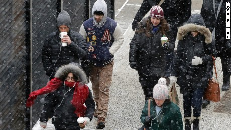 A light snow falls on pedestrians, Monday, Jan. 26, 2015 in New York. The National Weather Service says accumulations of 18 to 24 inches are possible by Tuesday afternoon. (AP Photo/Mark Lennihan)