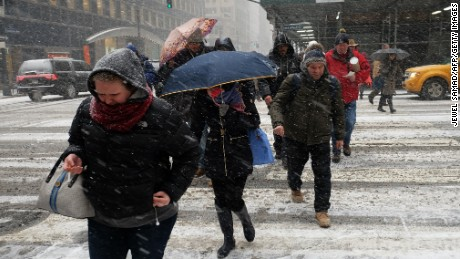 People cross a city street in a snow storm in New York on January 26, 2015.  Thousands of flights were canceled Monday as millions of Americans in the Northeast braced for a winter storm that New York's mayor warned could be one of the biggest blizzards in history. Snow, which was already falling across the region, is expected to accumulate steadily throughout the day before turning into a major storm expected to paralyze parts of New York and New England. Officials in states along the US East Coast have urged residents to stay home as they prepare for Winter Storm Juno, which could dump up to three feet (about a meter) of snow in some areas. AFP PHOTO/JEWEL SAMAD        (Photo credit should read JEWEL SAMAD/AFP/Getty Images)