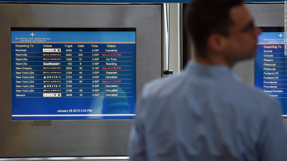 A man stands in front of a screen listing departing flights at Ronald Reagan Washington National Airport on January 26.