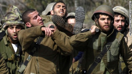 Israeli soldiers carry an injured soldier.