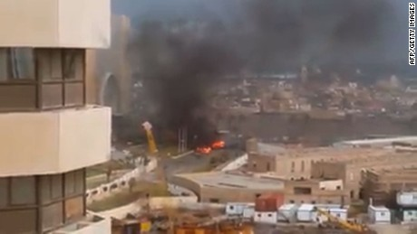 An image grab taken from an AFPTV video shows fire and smoke rising in front of the Corinthia hotel in Tripoli on January 27, 2015 after gunmen stormed the luxury hotel.