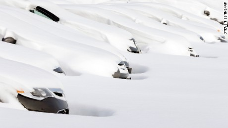 Cars sit buried by drifted snow January 28, 2015, at a used auto dealer in Norwood, Mass., after a winter snowstorm slammed New England on Tuesday.