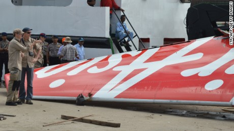 Caption:Foreign investigators (L) examine the tail of the AirAsia flight QZ8501 in Kumai on January 12, 2015, after debris from the crash was retrieved from the Java sea. Indonesian divers retrieved the flight data recorder of the AirAsia plane that went down in the Java Sea a fortnight ago with 162 people on board, a crucial breakthrough that should help explain what caused the crash. AFP PHOTO (Photo credit should read STR/AFP/Getty Images)