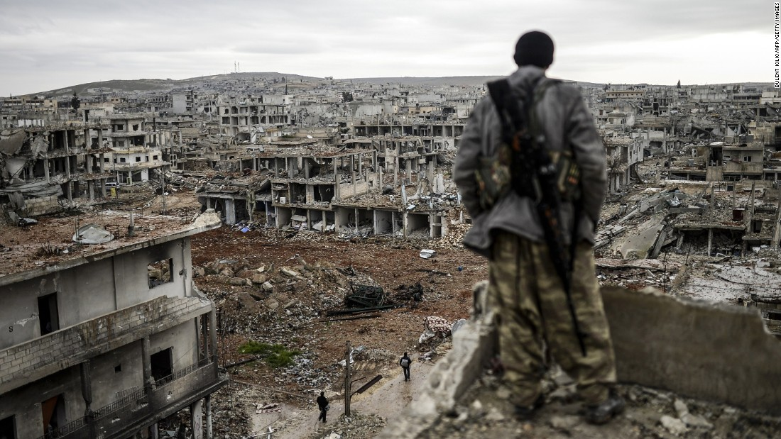 A Kurdish marksman looks over a destroyed area of Kobani, Syria, on Friday, January 30, after the city had been liberated from the ISIS militant group. Kobani, also known as Ayn al-Arab, had been under assault by ISIS since mid-September.