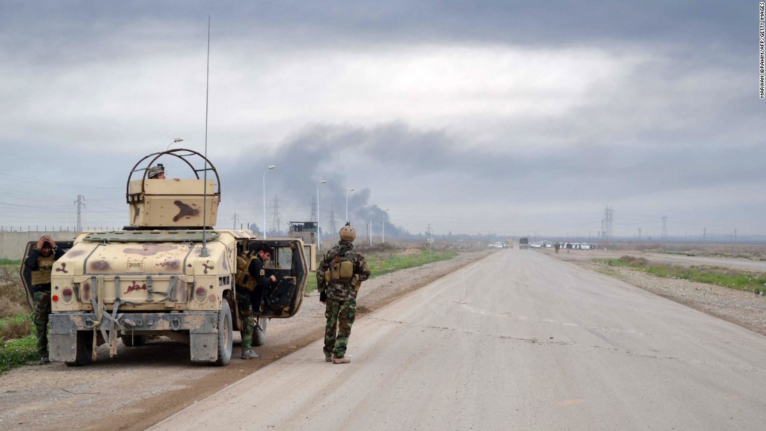 Smoke billows in the background as Kurdish Peshmerga fighters take position in Kirkuk, Iraq, on January 30.