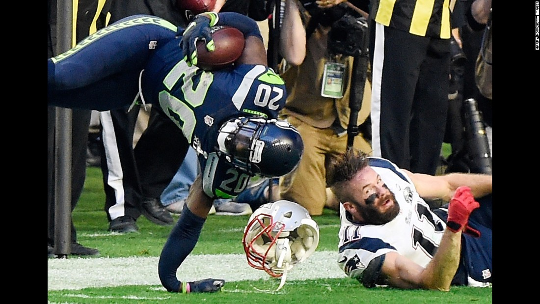 Seattle defensive back Jeremy Lane suffers a broken arm after he intercepted Brady and was tackled by Edelman, right.