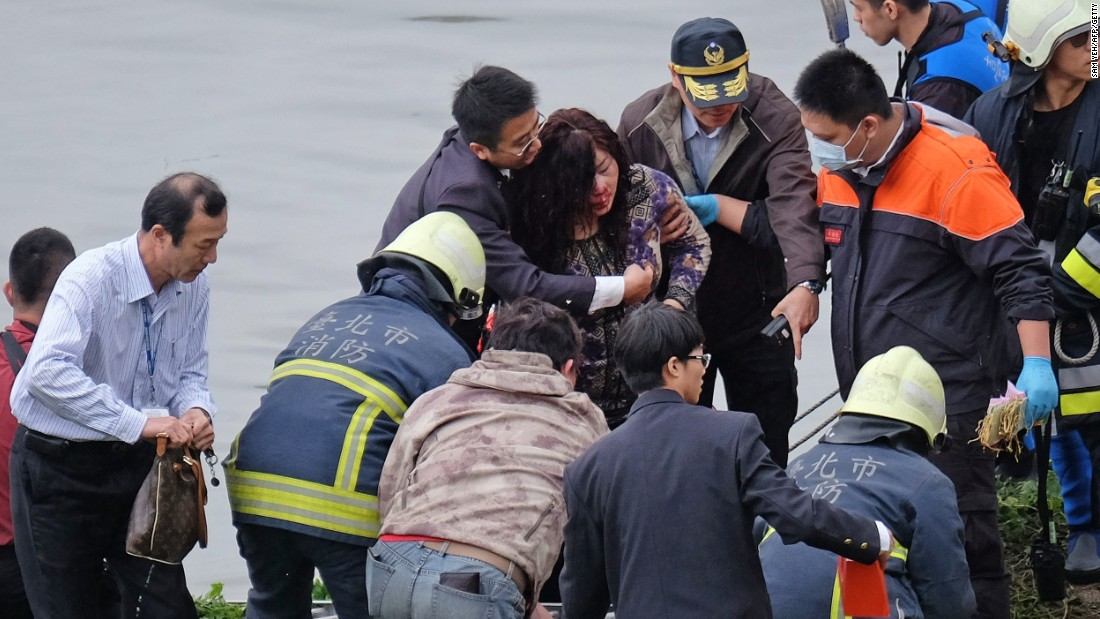Emergency personnel help an injured passenger onto land on February 4.