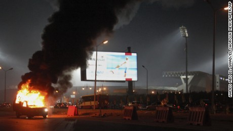 A pickup truck bursts into flames outside the stadium.