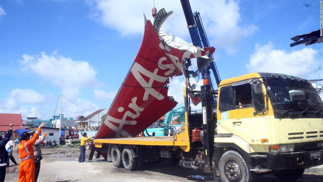 Workers load the tail of the plane onto a truck February 7 at the Kumai seaport.