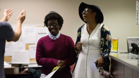 The room cheers for Shante Wolfe, left, and Tori Sisson, right after they are the first couple int the county to file their marriage license, Monday, Feb. 9, 2015, in Montgomery, Ala. Alabama began issuing marriage licenses to same-sex couples Monday despite an 11th-hour attempt from the state's chief justice to block the weddings. Alabama is the 37th state to allow gays and lesbians to wed. (AP Photo/Brynn Anderson/AP)