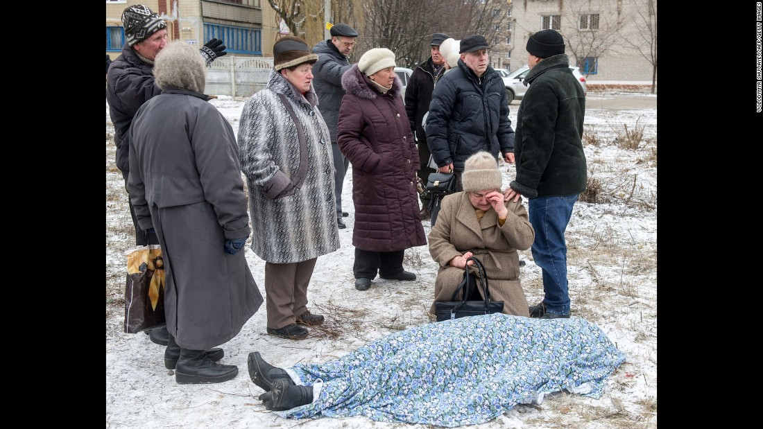 People stand beside the body of a woman killed during shelling in Kramatorsk, Ukraine, on Tuesday, February 10.