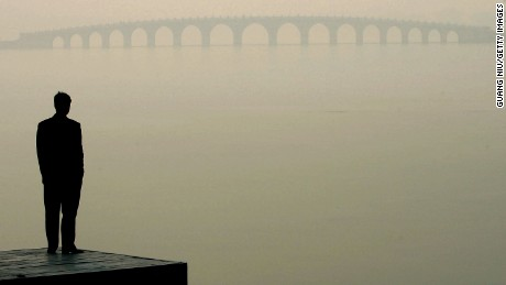A man looks towards a bridge in heavy fog on December 14, 2004 in Beijing, China. The bad weather has made it harder for Beijing to achieve the target of 18 clear-sky days in December, laid out by the environmental protection campaign, which requires the capital to have clear sky for 62 percent of the year, equivalent to 227 days. Beijing has pledged to cleanse the skies before the 2008 Olympic Games. (Photo by Guang Niu/Getty Images)