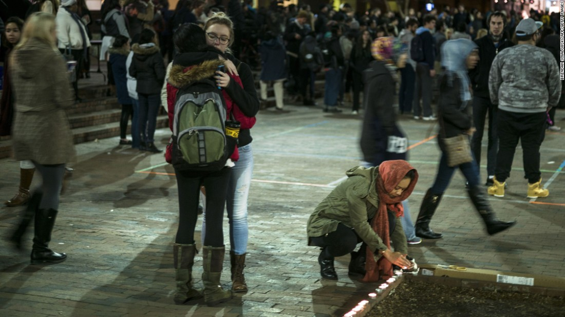 People embrace near a makeshift memorial at the close of a February 11 vigil.
