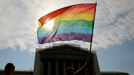 WASHINGTON, DC - JUNE 24: Gay rights activist Vin Testa of DC waves a flag in front of the U.S. Supreme Court building June 24, 2013 in Washington DC. The high court is expected to rule this week on some high profile decisions including California's Proposition 8, the controversial ballot initiative that defines marriage as between a man and a woman. (Photo by Win McNamee/Getty Images)