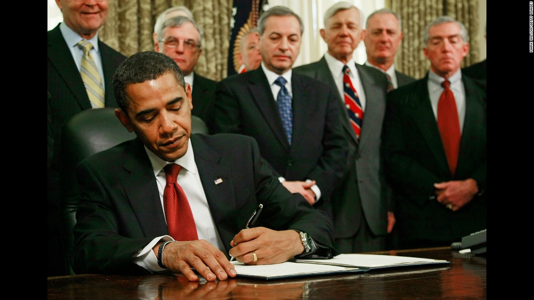As retired military officers stand behind him, Obama signs an executive order to close down the detention center at Guantanamo Bay in January 2009.