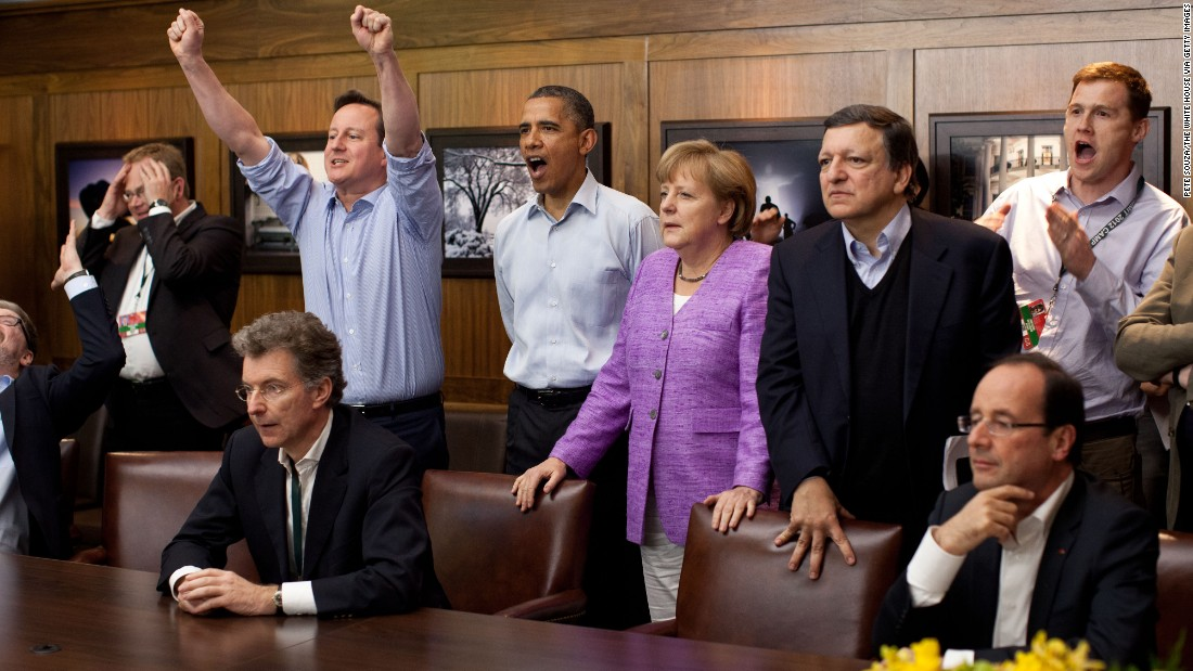 British Prime Minister David Cameron, Obama, German Chancellor Angela Merkel, and others watch the overtime shootout of the Champions League final soccer match between Chelsea and Bayern Munich in the Laurel Cabin conference room at Camp David, Maryland, during a G8 Summit in May 2012.