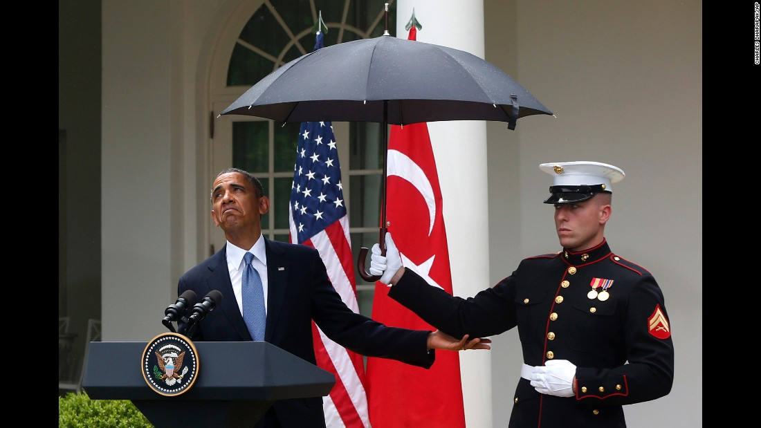 Obama adjusts an umbrella held by a Marine during a news conference with Turkish Prime Minister Recep Tayyip Erdogan in the Rose Garden of the White House in May 2013.