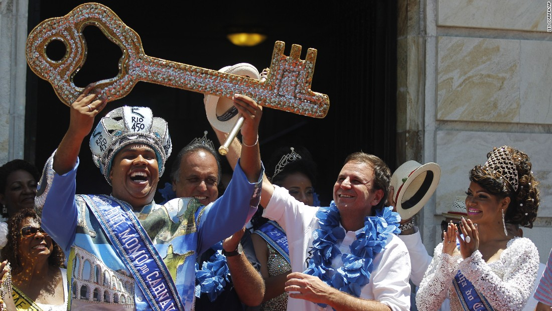 "The 2015 Carnival King, ""King Momo"" Wilson Dias da Costa Neto, holds up the key to the city of Rio de Janeiro with Mayor Eduardo Paes, center, and Carnival Queen Clara Paixao, right, on February 13."