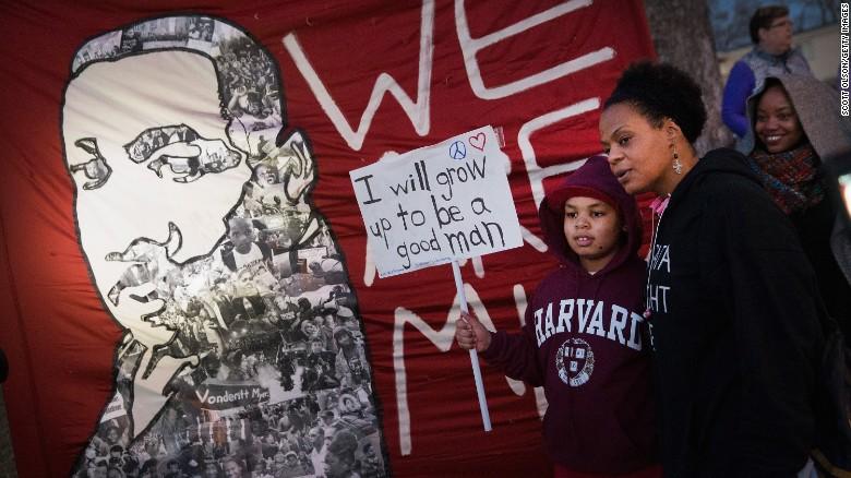 Demonstrators protest next to a Michael Brown memorial in Ferguson, Missouri