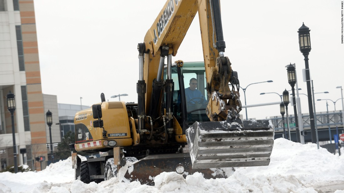 Heavy machinery works on snow banks on East Service Street in Boston on February 14.