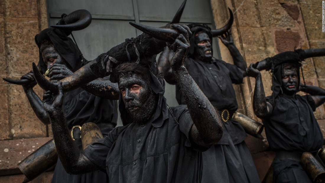 People with their faces covered in oil and soot carry bull horns as they represent devils at a Carnival festival in Luzon, Spain, on February 14.