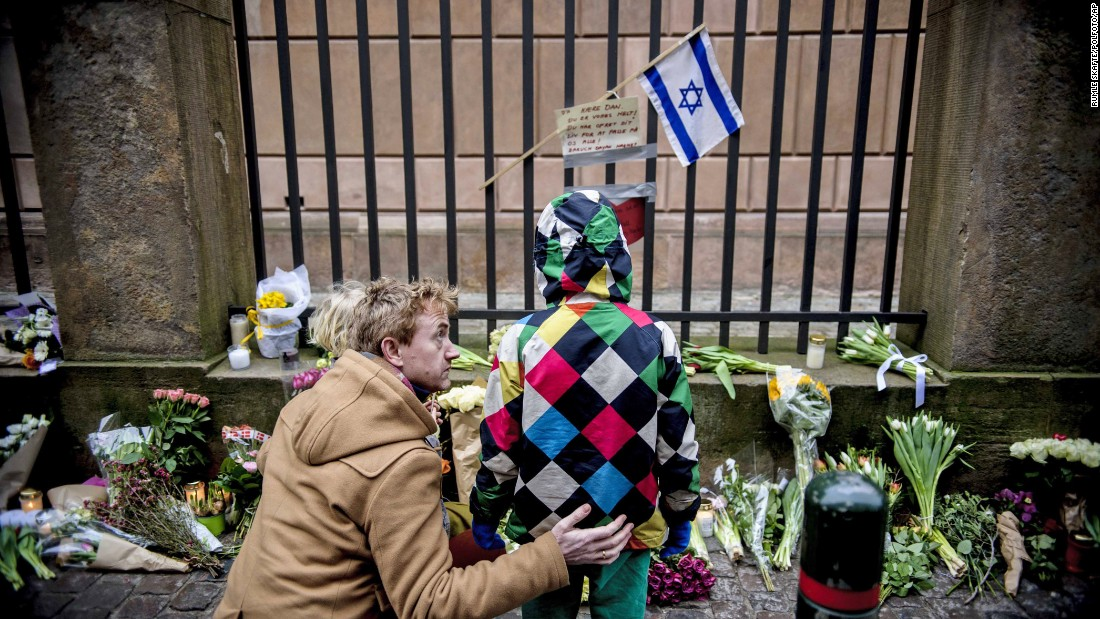 People look at a makeshift memorial on Sunday, February 15, outside a synagogue where an attack took place Saturday in Copenhagen, Denmark. Danish police shot and killed a man early Sunday suspected of carrying out shooting attacks at a free speech event and then at a Copenhagen synagogue.