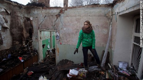 A woman salvages items from the rubble of a destroyed clinic where she had worked in Opytne, Ukraine, on February 15.