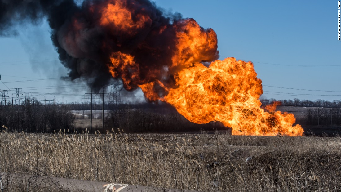 A gas pipe burns after being struck by shelling in Myronivskyi.