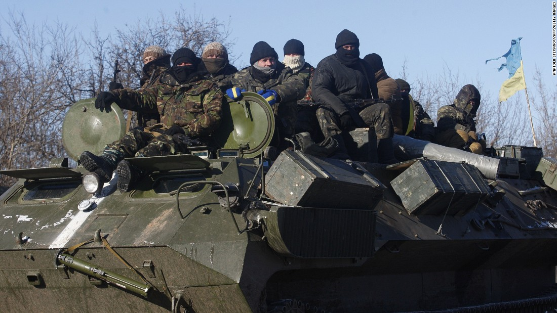 Ukrainian servicemen ride on top of an armored personnel carrier on the way from Artemivsk to Debaltseve.