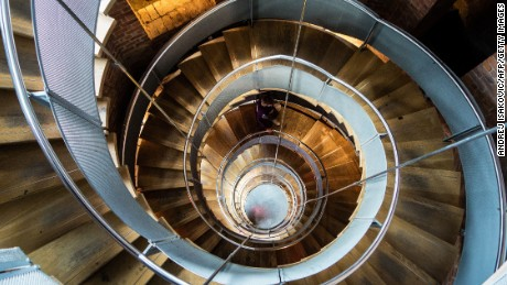 A woman climbs the spiral stairs at the Lighthouse, formerly the Glasgow Herald building, designed by the architect Charles Rennie Mackintosh.