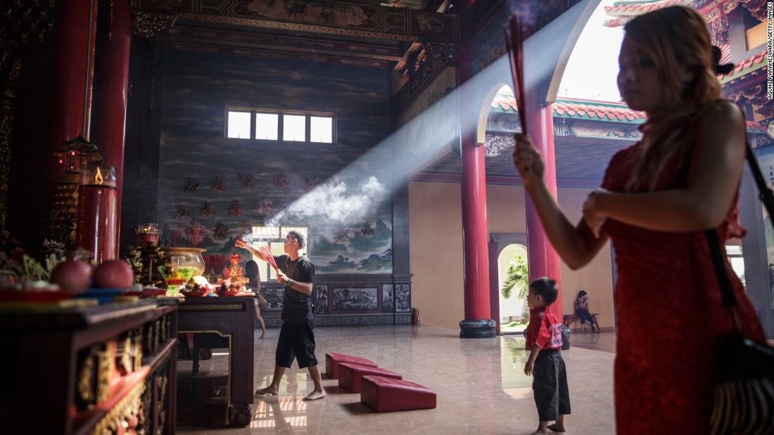 A man lights incense sticks at a temple in Denpasar, Indonesia, on February 19.