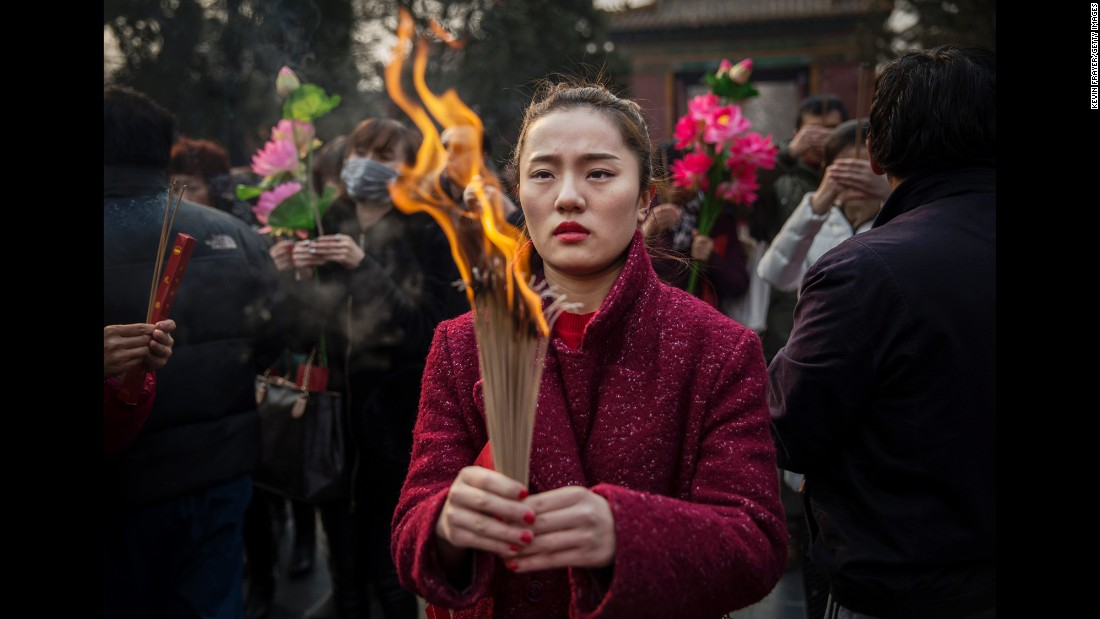 A woman holds incense at a Beijing temple February 19.