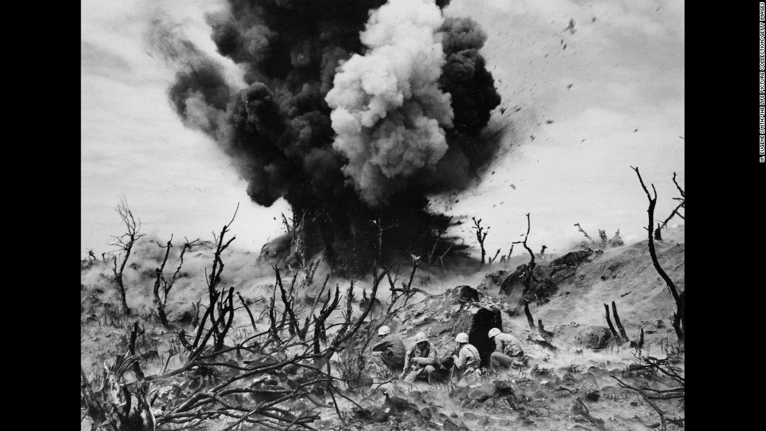 U.S. Marines take cover as a cave is blown up on Iwo Jima.