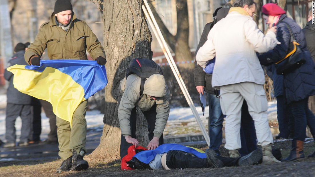 A man holds a Ukrainian flag as he covers a victim of an explosion in Kharkiv, Ukraine, on Sunday, February 22. The explosion during a peaceful protest left two dead and 15 wounded.