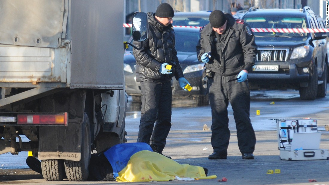 Investigators work at the site of the explosion, where the body of a victim is covered with a Ukrainian flag, in Kharkiv, Ukraine, on February 22.