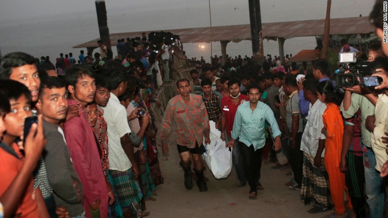 Rescue workers carry bodies after a ferry capsized after being hit by a boat on Sunday in Bangladesh.