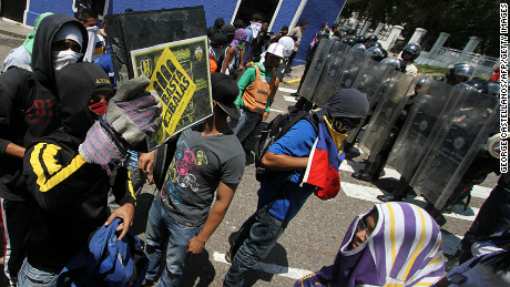 A group of students stand in front of a line of riot policemen during a protest against Venezuelan President Nicolas Maduro's government in San Cristobal, Venezuela on February 24, 2015. Venezuelan prosecutors said they would charge a policeman in connection with the death of a 14-year-old boy who was killed during the protest against the country's economic crisis. AFP PHOTO / GEORGE CASTELLANO (Photo credit should read George CASTELLANOS/AFP/Getty Images)