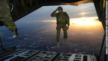 A U.S. Soldier assigned to 1st Battalion, 10th Special Forces Group (Airborne) salutes his fellow Soldiers while jumping out of a C-130 Hercules aircraft over a drop zone in Germany, Feb. 24.
