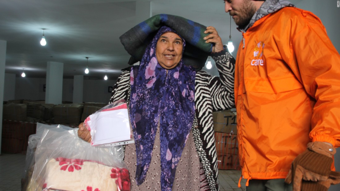 A CARE aid worker provides relief supplies for winter to a Syrian refugee in Turkey.  Many refugees struggle to find winter clothes, boots and blankets.
