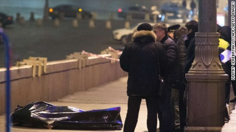 Russian police investigators stand near the body of Russian opposition leader Boris Nemtsov, covered by plastic, on Bolshoi Moskvoretsky bridge near St. Basil cathedral in central Moscow on February 28, 2015. Russian opposition leader Boris Nemtsov, a fierce critic of President Boris Yeltsin, was shot dead in central Moscow ahead of a major opposition rally this weekend, investigators and police said. AFP PHOTO / DMITRY SERERYAKOV (Photo credit should read DMITRY SEREBRYAKOV/AFP/Getty Images)