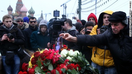 A man places a picture on flowers on February 28, 2015 at the spot, where Russian opposition leader Boris Nemtsov was shot dead, near Saint-Basil's Cathedral, in the center of Moscow. Nemtsov, a fierce critic of President Vladimir Putin, was gunned down while walking in sight of the Kremlin late on February 27, prompting an international chorus of condemnation.