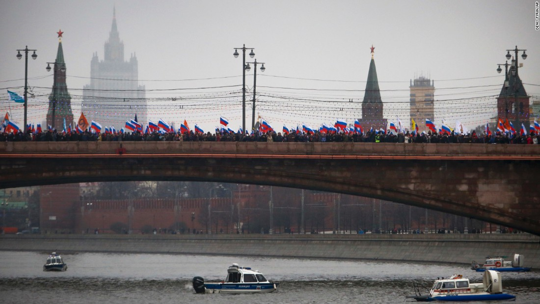 Watched by police in boats on the Moskva River, crowds march across a bridge in Moscow on March 1.