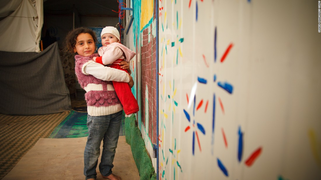 Hala, 4 months, is held by her big sister Mais, 5, in the Zaatari Camp in Jordan. Her young parents and three siblings arrived in the camp two years ago from Dara'a, Syria. Mercy Corps is helping about  3.7 million people affected by the Syrian crisis, including 2.7 million inside Syria.