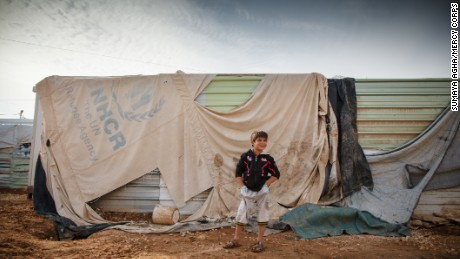"2015 February — Jordan. Zaatari Camp for Syrian Refugees. Precocious Omer (7) and his family are from Marabeh in the Dara'a governorate of Syria. There are five girls and two boys in the family. Omer is the youngest at 7 and the oldest is 24. They arrived in camp two years ago. Omer says, ""Winter is not nice here. We step in mud and water. Snow is the worst part of winter here."""