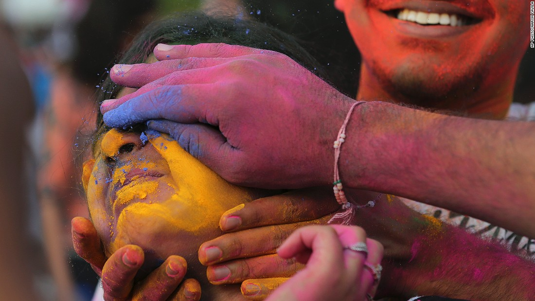 MARCH 2 - MANILA, PHILIPPINES: Revelers place colored powder on a woman's face as they celebrate the Holi festival in Pasay, south of Manila. The event is led by Indian nationals as they mark the spring occasion, also known as the festival of colors.