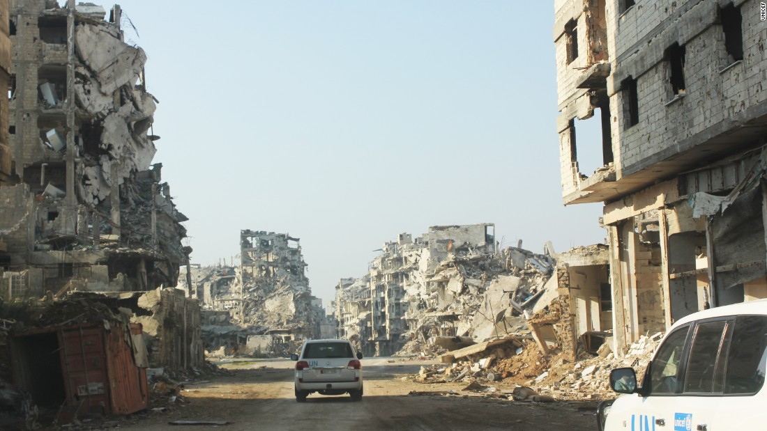 UNICEF vehicles travel a dusty road lined with remnants of buildings in the Old City of Homs, Syria. UNICEF has 380 staff working on the Syrian crisis, 180 inside Syria.